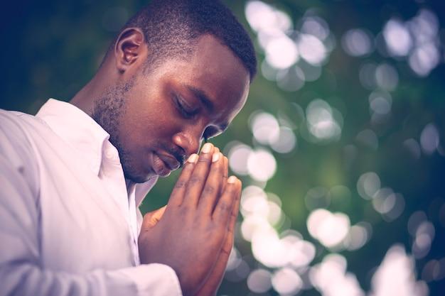 Afrikanischer mann, der für gott sei dank betet. Premium Fotos