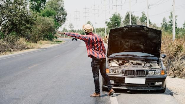Afrikanischer mann, der hände für hilfe anhebt, weil sein auto seite die landstraße defekt ist Premium Fotos