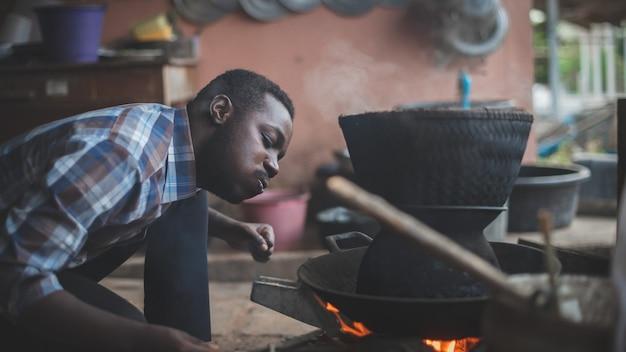 Afrikanischer mann, der sitzt, um feuer zu blasen, um reis zu kochen. 16: 9 art Premium Fotos