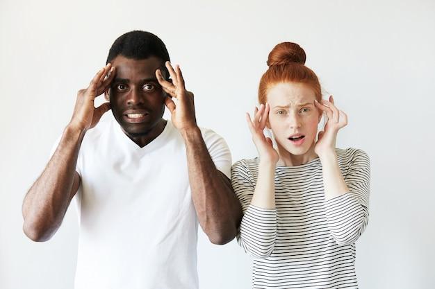 Afrikanischer mann im weißen t-shirt und rothaarige kaukasische frau im gestreiften oberteil Kostenlose Fotos