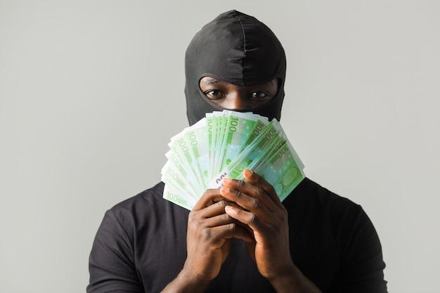 Afrikanischer mann in einer schwarzen räubermaske und in einem schwarzen t-shirt an einer grauen wand mit euro in den händen Premium Fotos