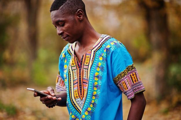 Afrikanischer mann in traditionellem hemd afrikas auf herbstpark. Premium Fotos