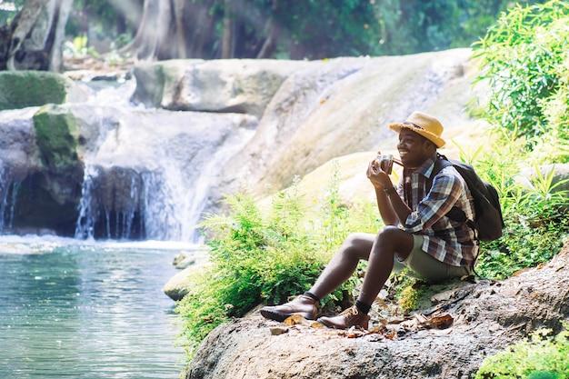 Afrikanischer mann-reisender mit dem halten der filmkamera und der entspannenden freiheit am wasserfall Premium Fotos
