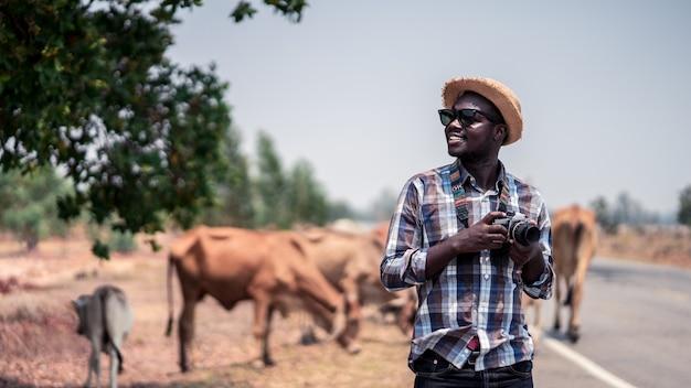 Afrikanischer mannphotograph, der in landschaft mit art cows.16: 9 reist Premium Fotos