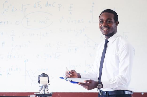 Afrikanischer naturlehrer, der in der stammklasse mit mikroskop unterrichtet und lächelt. Premium Fotos