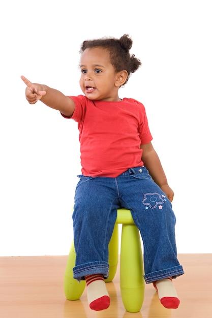 Afrikanisches baby, das auf einem schemel auf einem weißen hintergrund sitzt Premium Fotos
