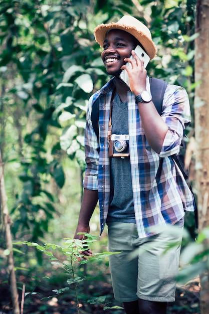 Afrikanisches mannreisendlächeln und entspannen sich im dschungel Premium Fotos