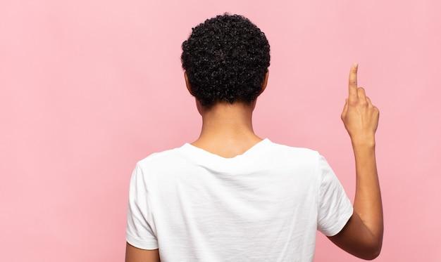 Afro junge schwarze frau, die steht und auf objekt auf kopienraum zeigt Premium Fotos