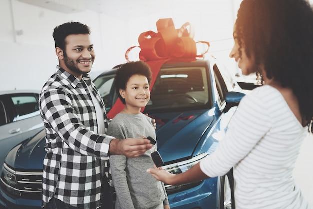 Afro man präsentiert auto zu frau jubiläumsgeschenk. Premium Fotos