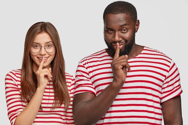 Afroamerikaner junger mann und europäisches mädchen machen schweigegeste, zeigefinger über mund halten Kostenlose Fotos