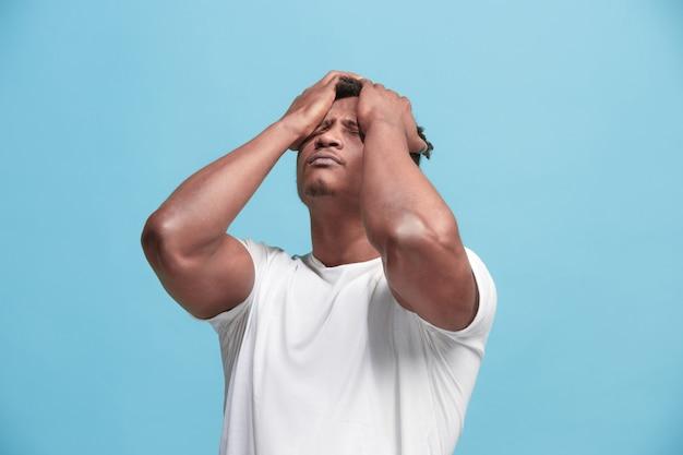Afroamerikaner mann, der kopfschmerzen hat. isoliert über blauem hintergrund. Kostenlose Fotos