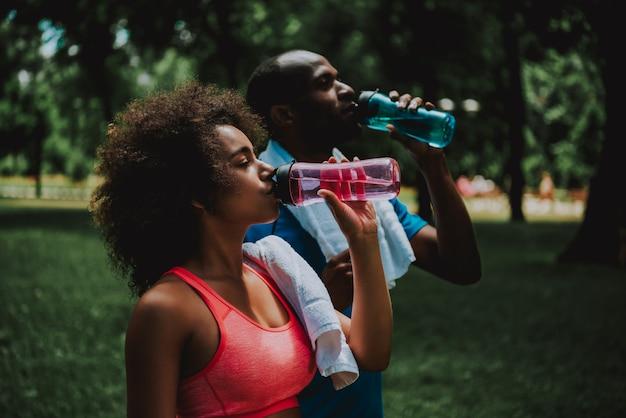 Afroamerikaner-paar-trinkwasser im park. Premium Fotos