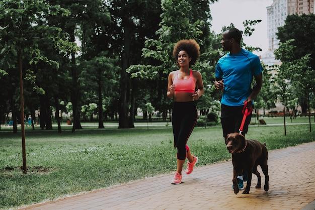 Afroamerikaner-paare in gehendem hund der sportkleidung Premium Fotos