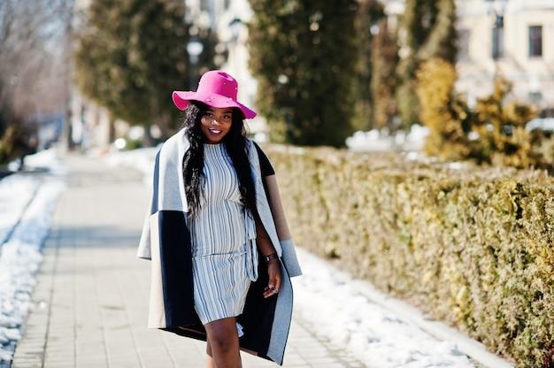 Afroamerikanerfrau am hut und am mantel mit telefon gehend an den straßen. Premium Fotos