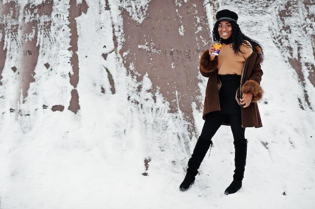 Afroamerikanerfrau im schaffellmantel und in der kappe warf am wintertag gegen schneebedeckten hintergrund mit tasse kaffee auf. Premium Fotos
