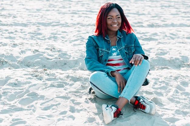 Afroamerikanerfrau mit den überfahrtbeinen, die auf sand sitzen Kostenlose Fotos