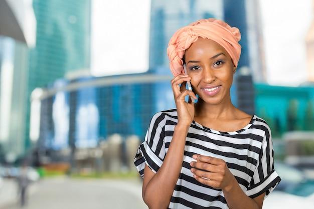 Afroamerikanerfrau mit einem handy Premium Fotos