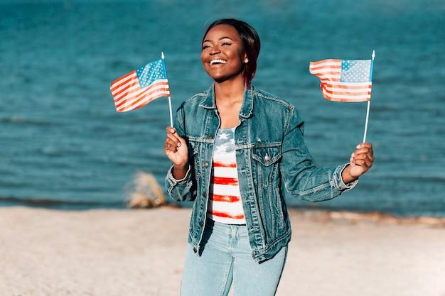 Afroamerikanerfrau, welche die amerikanischen flaggen stehen auf küste hält Kostenlose Fotos