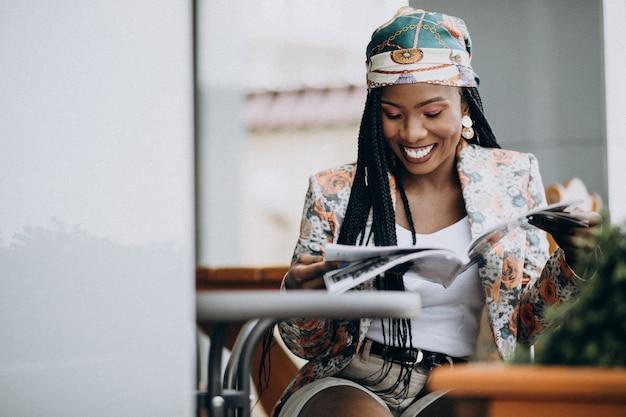 Afroamerikanerfrauen-lesezeitschrift in einem café Kostenlose Fotos
