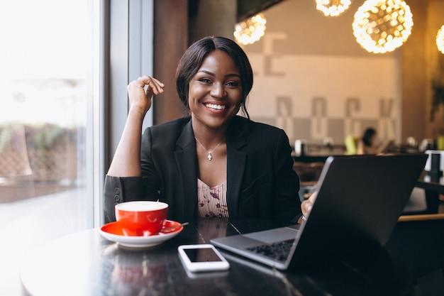 Afroamerikanergeschäftsfrau, die in einem café arbeitet Kostenlose Fotos
