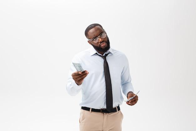 Afroamerikanergeschäftsmann, der bargeld und ernste schauende kamera hält. innen, lokalisiert auf grauem hintergrund. Premium Fotos
