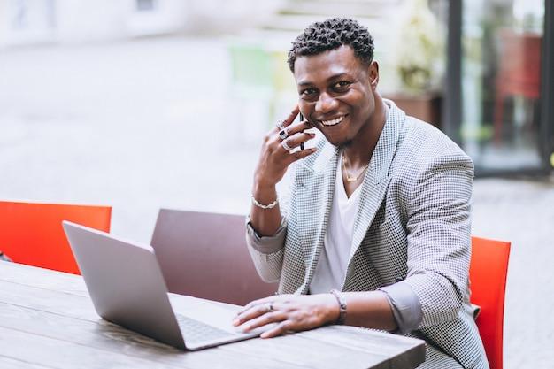 Afroamerikanergeschäftsmann, der laptop in einem café verwendet Kostenlose Fotos
