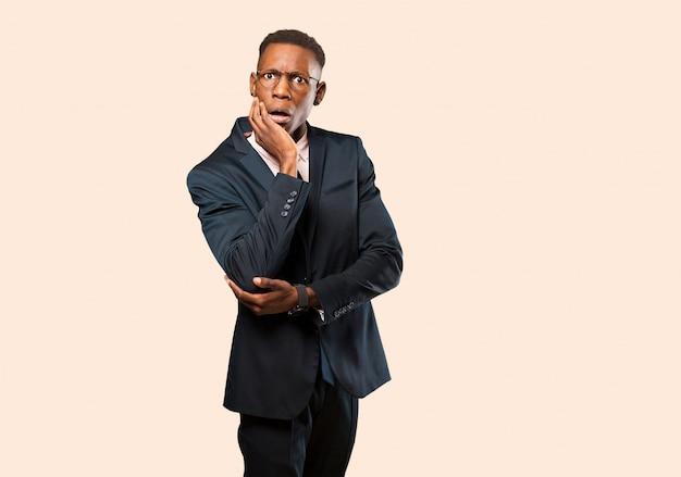 Afroamerikanergeschäftsmann mit offenem mund im schock und im unglauben, wenn die hand auf backe und arm gekreuzt ist, gefühl betäubt und gegen beige wand überrascht Premium Fotos