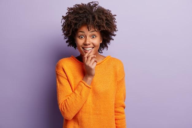 Afroamerikanerin im orangefarbenen pullover Kostenlose Fotos