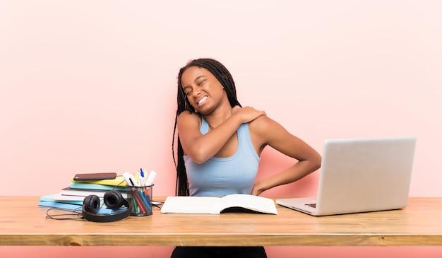 Afroamerikanerjugendlich-studentenmädchen mit dem langen umsponnenen haar an ihrem arbeitsplatz, der unter den schmerz in der schulter leidet Premium Fotos