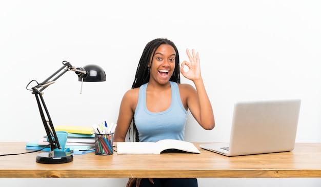Afroamerikanerjugendlich-studentenmädchen mit dem langen umsponnenen haar an ihrem arbeitsplatz überrascht und okayzeichen zeigend Premium Fotos