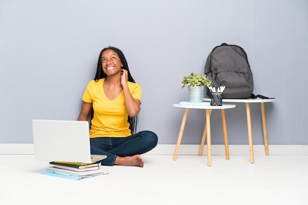 Afroamerikanerjugendlich-studentenmädchen mit dem langen umsponnenen haar sitzend auf dem boden eine idee denkend Premium Fotos