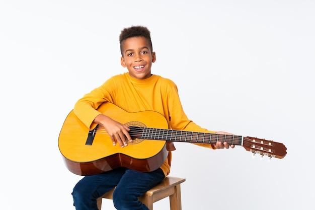 Afroamerikanerjunge mit gitarre über getrenntem weiß Premium Fotos