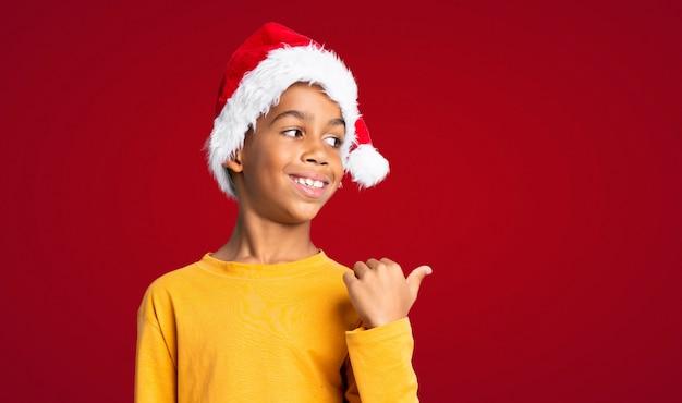 Afroamerikanerjunge mit weihnachtshut zeigend auf die seite, um ein produkt über roter wand darzustellen Premium Fotos