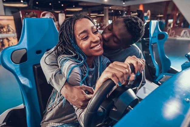 Afroamerikanermädchen, das blaues auto in der säulengang reitet. Premium Fotos