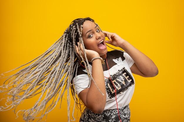 Afroamerikanermädchen, das musik auf kopfhörer auf gelb hört Premium Fotos