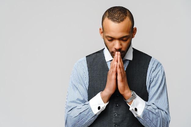 Afroamerikanermann, der hände im gebet hält und auf besseres hofft. Premium Fotos