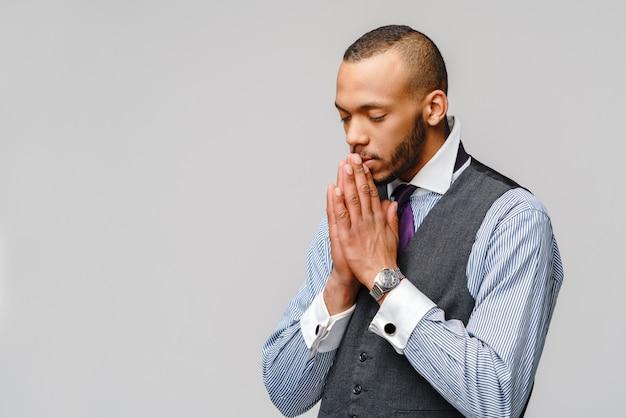 Afroamerikanermann, der hände im gebet hält und auf besseres hofft Premium Fotos