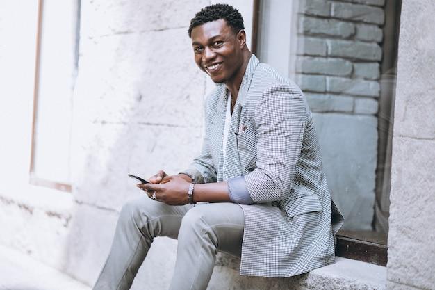 Afroamerikanermann, der telefon verwendet Kostenlose Fotos