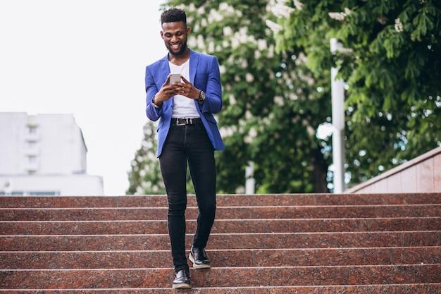 Afroamerikanermann in der blauen jacke unter verwendung des telefons Kostenlose Fotos