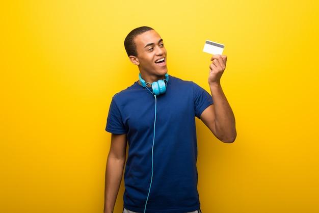 Afroamerikanermann mit blauem t-shirt auf dem gelben hintergrund, der eine kreditkarte und ein denken hält Premium Fotos