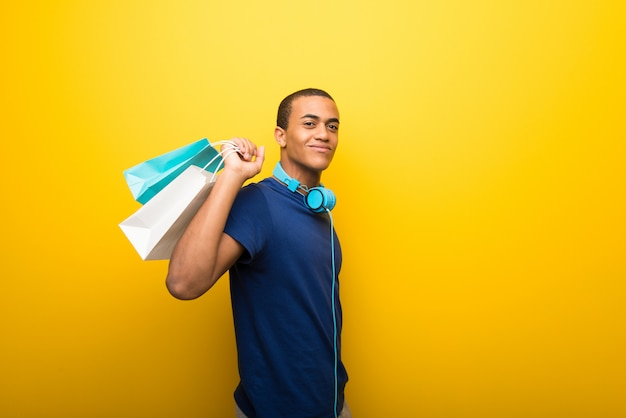 Afroamerikanermann mit blauem t-shirt auf dem gelben hintergrund, der viele einkaufstaschen hält Premium Fotos