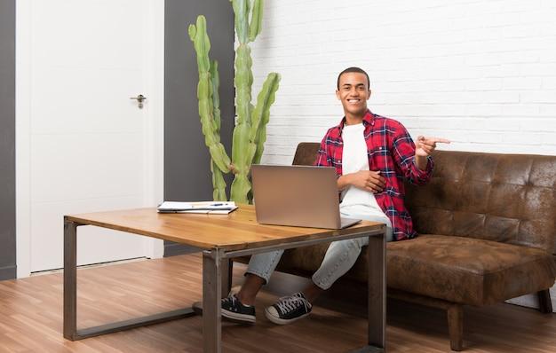 Afroamerikanermann mit laptop im wohnzimmer finger auf die seite in seitlicher position zeigend Premium Fotos