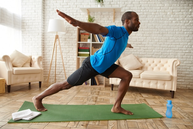Afroamerikanermann übt fortgeschrittenes yoga zu hause. Premium Fotos