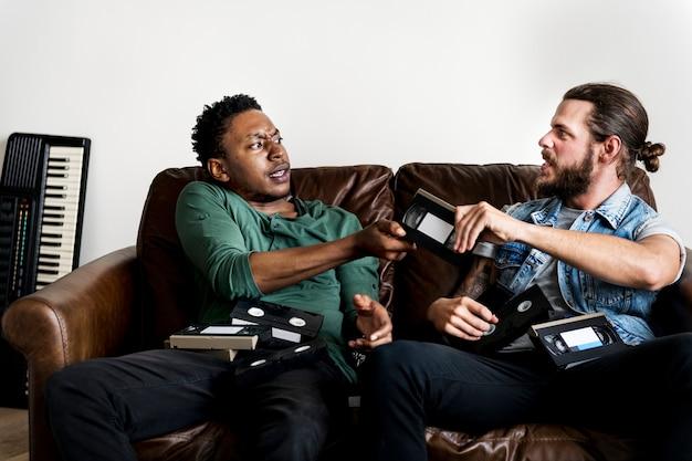 Afroamerikanermann und kaukasische männliche hippies, die über vhs-videoband kämpfen Premium Fotos