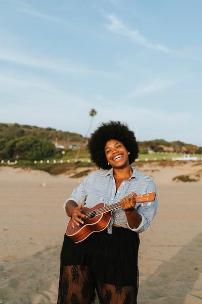 Afroamerikanermusiker, der ukulele am strand spielt Premium Fotos