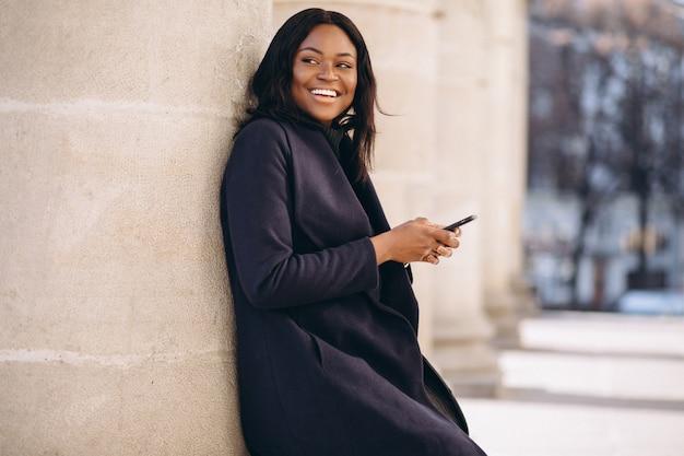 Afroamerikanerstudentenmädchen mit telefon durch die universität Kostenlose Fotos