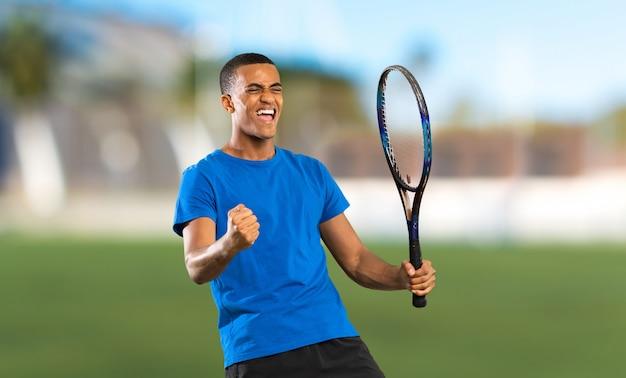 Afroamerikanertennisspielermann an draußen Premium Fotos