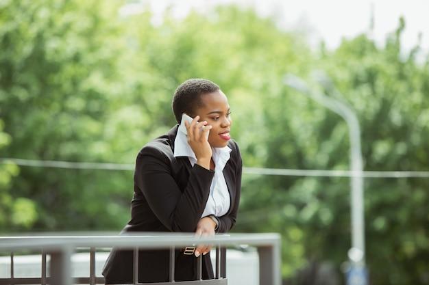 Afroamerikanische geschäftsfrau in bürokleidung lächelnd, sieht selbstbewusst und glücklich aus, beschäftigt Kostenlose Fotos