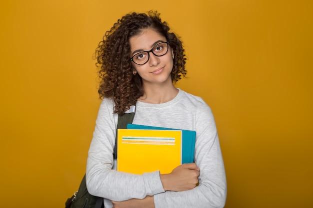 Afroamerikanische studentin des porträts in den gläsern mit büchern auf einem gelben hintergrund. Premium Fotos