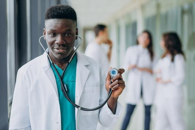 Afroamerikanischer arzt mann mit stethoskop, stehend im korridor des krankenhauses Kostenlose Fotos